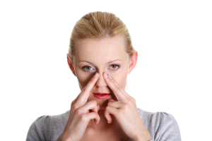 Young woman placing her fingers on the sides of her nose