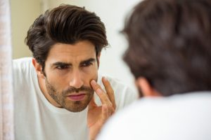 Handsome man looking in mirror touching face